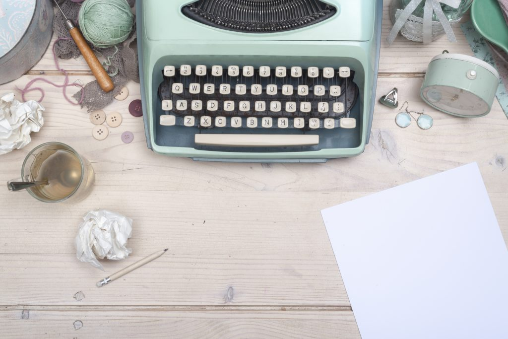 An old blue typewriter on a wooden desk